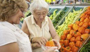 Mamie qui achète des légumes