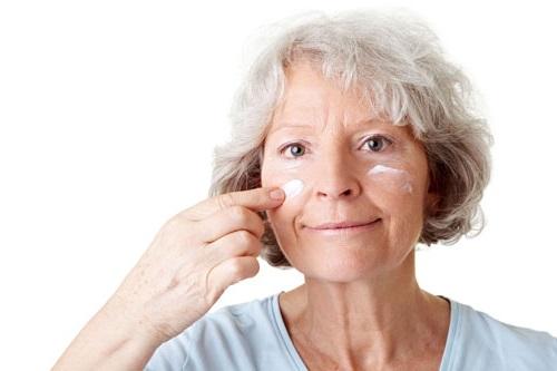 Senior s'appliquant de la crème sur le visage