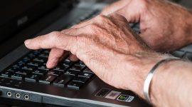 Senior tapant sur un clavier d'ordinateur portable