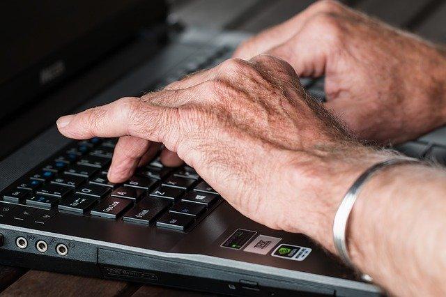 Senior tapant à l'ordinateur